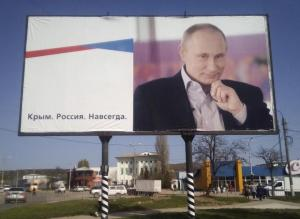 """A billboard with a portrait of Russian President Vladimir Putin is displayed on a street in Kerch, Crimea, April 7, 2016.  The board reads: """"Crimea. Russia. Forever.""""     REUTERS/Andrew Osborn/File Photo"""